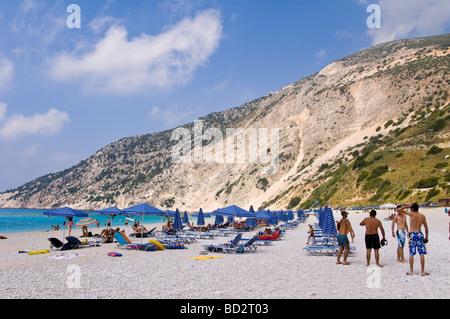Entspannen Sie sich auf Liegestühlen unter Sonnenschirmen auf Myrtos Strand mit blauer Flagge auf der griechischen - Stockfoto