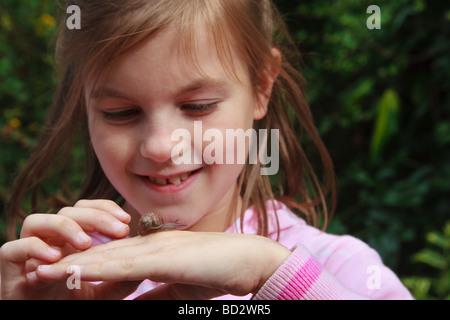 Junges Mädchen mit Schnecke kriecht in die hand - Stockfoto