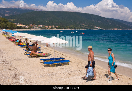 Entspannen Sie sich auf Liegestühlen unter Sonnenschirmen am sandigen Strand von Sami auf der griechischen Mittelmeer - Stockfoto