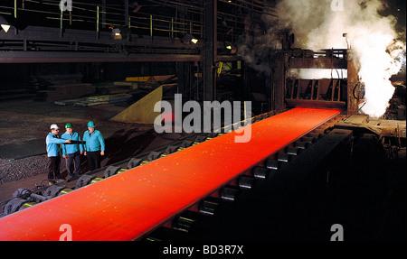 Drei Führungskräfte sehen den Walzprozess des flüssigen Stahls in einer Pennsylvania Stahl-Mühle - Stockfoto