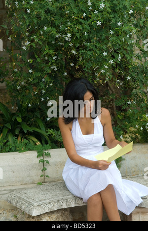 Junge Frau liest einen Brief im Garten - Stockfoto