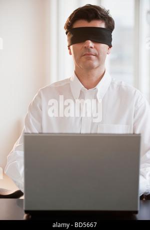 Geschäftsmann mit Laptop und mit verbundenen Augen - Stockfoto