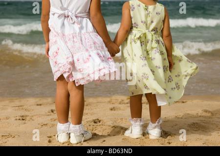 Zwei kleine Mädchen Hand in Hand am Strand - Stockfoto