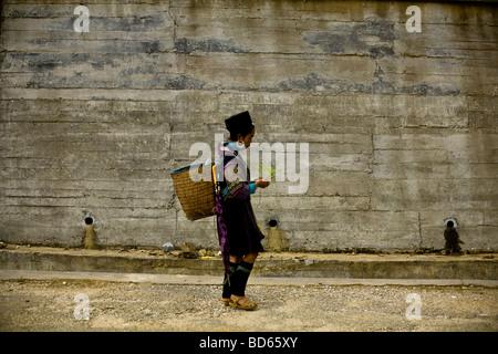 Eine Black Hmong-Frau geht entlang vorbei an einer neuen Betonmauer in Sapa in Nordvietnam - Stockfoto