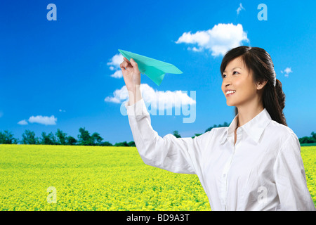 Chinesisches Mädchen spielen Papierflieger im Feld - Stockfoto