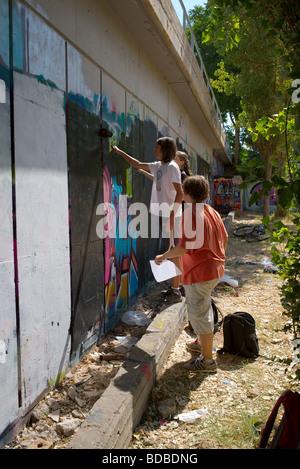 ein junger Mann auf der Suche auf, wie zwei junge Männer Betonwand in der Vorbereitung auf ihre neue Graffiti schwarz - Stockfoto