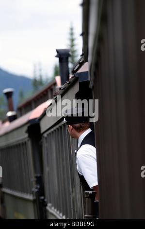 Skagway, Alaska, die Bremse Dirigent auf der White Pass and Yukon Route Railway lehnt sich zwischen Autos für eine - Stockfoto