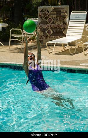 Junior high Hispanic Mädchen fangen Ball in Swimming poo Kind Kinder Spaß HERR - Stockfoto