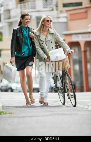 Zwei Frauen gehen mit Einkaufstüten - Stockfoto
