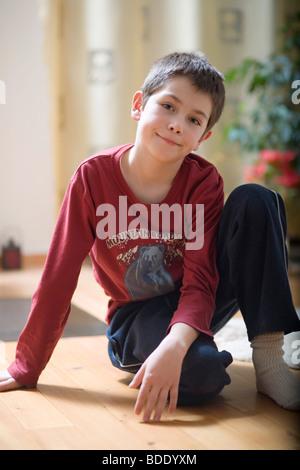 Porträt eines kleinen Jungen auf dem Boden sitzend - Stockfoto