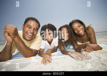 Vater und Mutter spielen am Strand mit Familie - Stockfoto