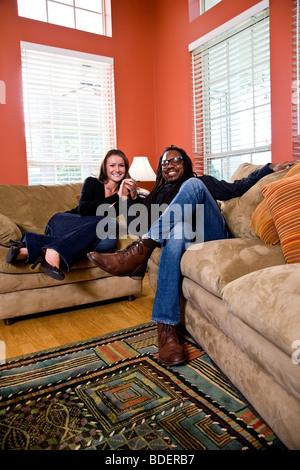 Interracial paar sitzt auf der Couch im Wohnzimmer - Stockfoto