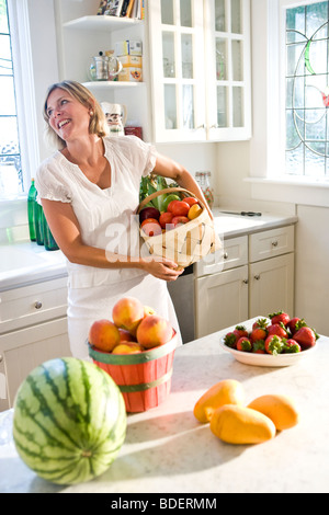 Mitte erwachsenen Frau hält Korb mit frischem Obst und Gemüse in der Küche - Stockfoto