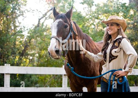 Junge Frau mit Pferd am Bauernhof - Stockfoto