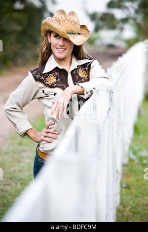 Porträt des jungen Cowgirl stehend nahe bei Zaun auf Bauernhof - Stockfoto