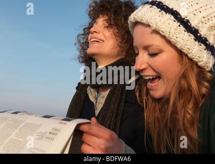 Frauen halten Zeitung, lachen - Stockfoto