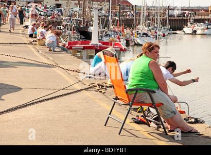 Menschen säumen die Kai-Seite bei Wells-Next-the-Sea Fishing für Krabben - Stockfoto