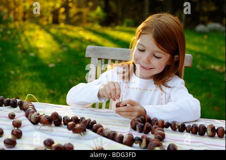 Mädchen spielt im Garten mit Kastanien, Kastanien Igel, Kastanien Figuren - Stockfoto