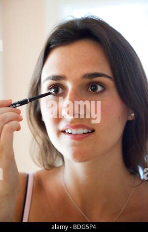 junge Frau beim Eye Liner Schminken - Stockfoto