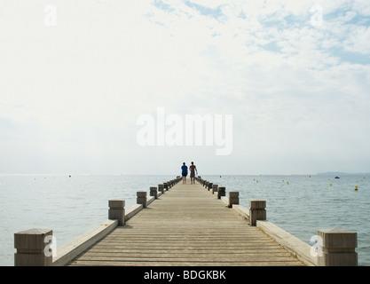 Paare, die auf kleine hölzerne Pier Blick auf das Meer - Stockfoto