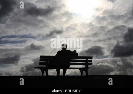 Silhouette eines Mannes sitzen auf einer bank - Stockfoto
