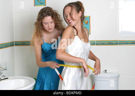 Schlanke Schwestern mit Maßband um Taille - Stockfoto