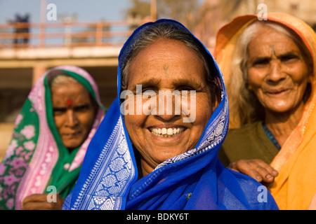 Drei Hindu-Frauen tragen Schals über ihren Köpfen stehen auf der Dasawamedh Ghat in der Stadt von Varanasi, Indien. - Stockfoto