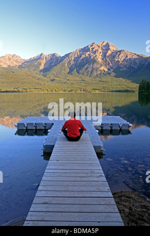 Mittleren Alters männlichen meditieren auf dock am Pyramid Lake, Jasper Nationalpark, Alberta, Kanada. - Stockfoto