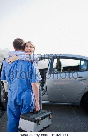 Frau umarmt ankommenden Mechaniker - Stockfoto