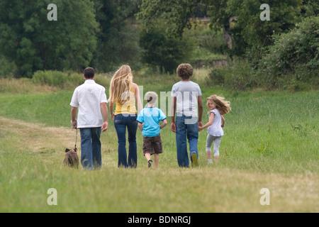 Rückseite des jungen Familie gehen in der Landschaft mit gestromt Staffordshire Bull Terrier Hund, Tochter Kopf, - Stockfoto