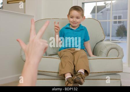 """Junge Unterzeichnung die Zahl """"3"""" in amerikanischer Gebärdensprache - Stockfoto"""