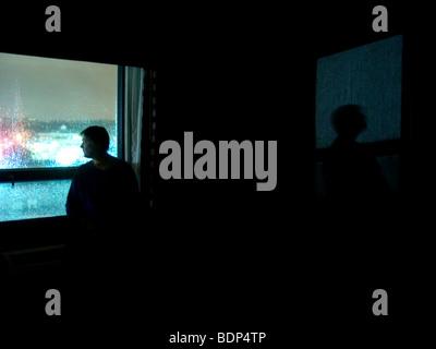 Eine Figur stehen in einem dunklen Raum auf der Suche unserer eines Fensters - Stockfoto