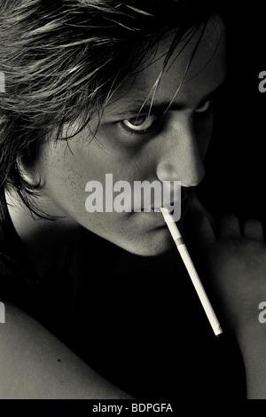 Das Gesicht eines jungen Mannes, der eine lange Zigarette rauchen - Stockfoto