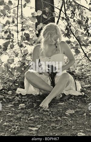 Eine junge Frau sitzt cross legged trägt ein weisses Sommerkleid hält ein rotes Herz sitzt unter einem Baum in s/w - Stockfoto