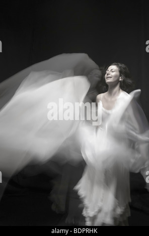 Eine junge Frau in einem weißen Kleid mit einem weißen Schleier in einer Unschärfe tanzen - Stockfoto