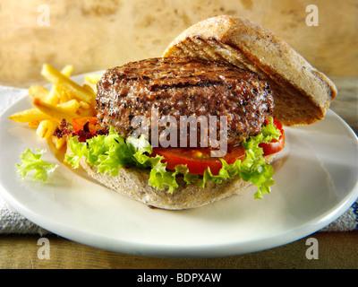 Gepfefferter Beef-Burger mit Pommes Frites und Vollkorn Brötchen - Stockfoto