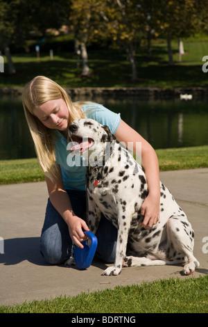 Kind umarmen Hund 11-13 Jahre alten Arm um Umarmen umarmen Dalmatinischen Hundebesitzer Zuneigung Vorderseite Profil - Stockfoto