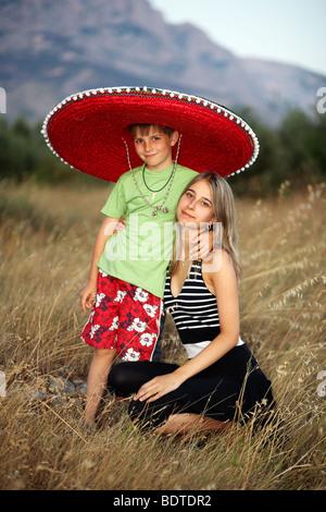 Zwei Geschwister, umgeben mit Stroh - Stockfoto
