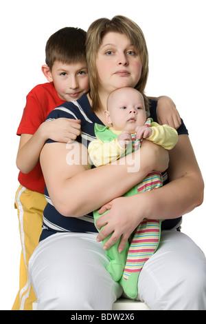 Mutter sitzt auf Achair und hält Kinder auf Händen, ältester Sohn umarmt sie für Schultern, isoliert auf weiss - Stockfoto