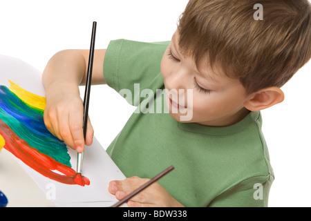 junge zieht mit Farben auf Papier mit Zunge hängen, isoliert auf weiss - Stockfoto