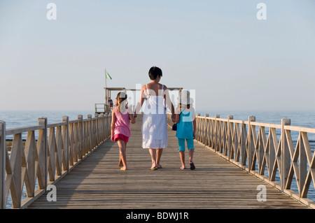 Mutter und zwei Töchter, die zu Fuß auf einem Steg - Stockfoto