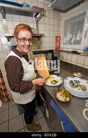 Chefkoch im Fonduerestaurant im Schweizer Dorf von Leukerbad Raclette, eine alpine Käsegericht - Stockfoto