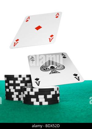 Zwei Asse fliegen über einen Stapel Chips auf dem Pokertisch. - Stockfoto