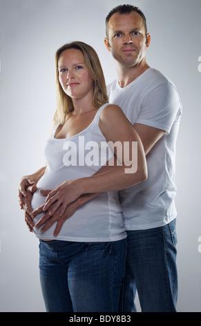 Mann umarmt schwangere Frau - Stockfoto