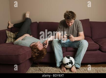 Jungen, die Benutzung von Mobiltelefonen - Stockfoto