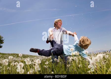 Vater schwingenden Sohn in Wiese - Stockfoto