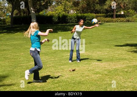 Zwei Teenie Mädchen hängen zusammen hängen, dass Junior high Mädchen Kugel zueinander werfen. 11-13 jährige Kinder - Stockfoto