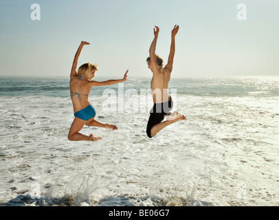 Paar springende in Wellen am Strand - Stockfoto