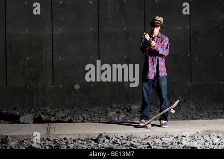 Skateboarder Befestigung seiner Manschette mit Board zu Füßen - Stockfoto
