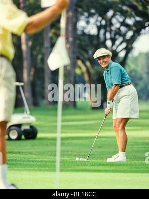 Ältere Frau Golfer setzen auf grün - Stockfoto